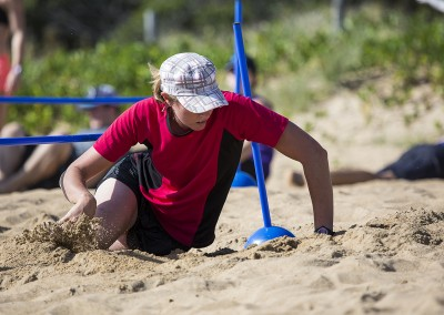 Jodie goes over and under on the soft sand obstacle during a beach workout.